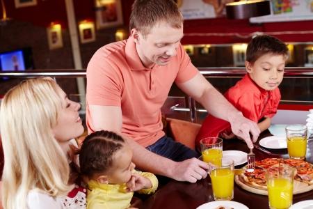 familia comiendo: Familia se reunieron para disfrutar de la pizza en la pizzería local Foto de archivo