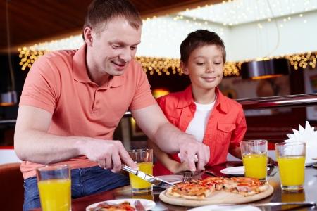 italienisches essen: Vater und Sohn eine Party nur f�r M�nner in der Pizzeria Lizenzfreie Bilder
