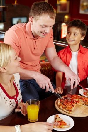 restaurante italiano: Familia espera de su padre para cortar una pizza apetitosa en pedazos Foto de archivo