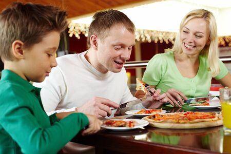 italienisches essen: Familie von drei essen leckere Pizza und Spa� haben