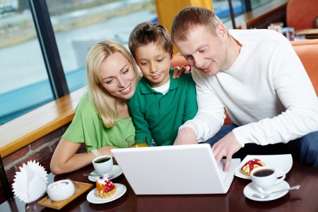 Parents and their male kid using the cafe wi-fi to surf the internet Stock Photo - 14442201