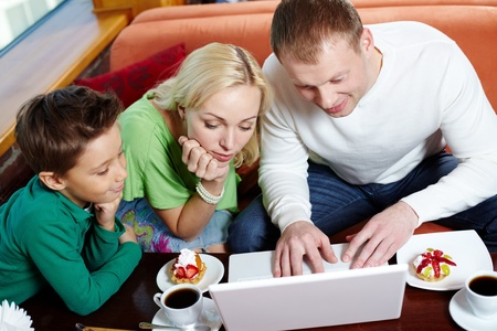 Happy modern family surfing the internet at the cafe photo