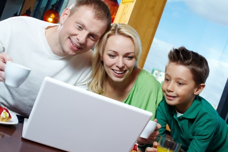 Family of three being amazed with the stuff displayed on the laptop screen photo