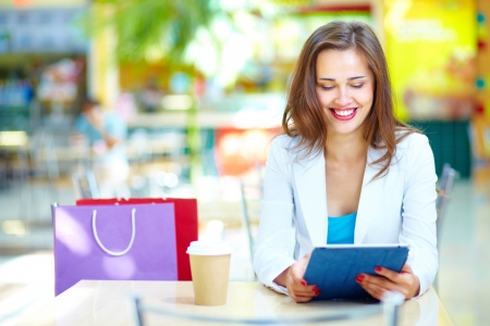 Shopping girl laughing looking at the screen of her portable device Stock Photo