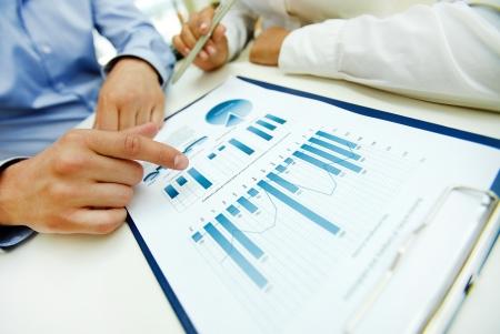 Close-up di grafici e diagrammi analizzati da uomini d'affari