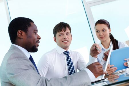Portrait of two employees listening to explanation of their colleague at meeting Stock Photo - 14462154