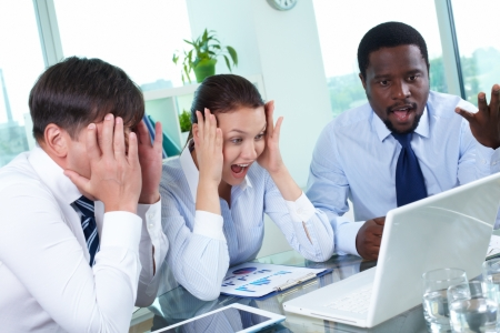 Three astonished colleagues looking at laptop monitor at meeting photo