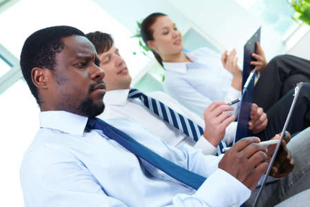 Portrait of successful business team making notes with their leader in front photo