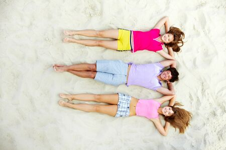 barefoot teens: Above angle of laughing teenage friends lying on sandy beach