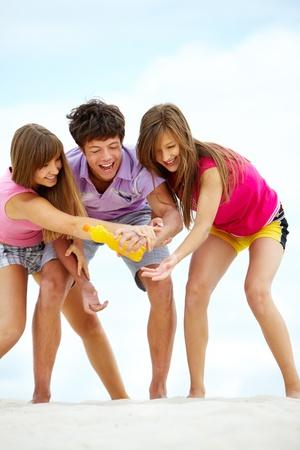 Portrait of three teenage friends having good time on sandy beach photo