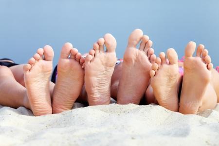 Soles of teenagers sunbathing on sandy beach photo