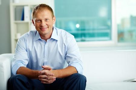 associates: Portrait of confident man sitting in office Stock Photo