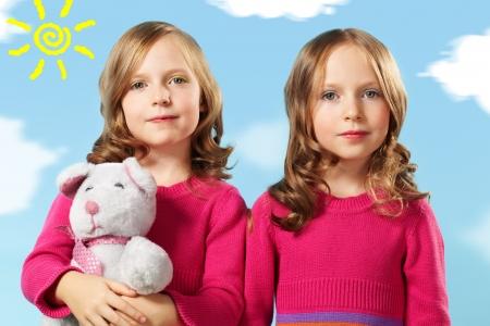 teddybear: Portrait of two smart girls in crimson clothes against blue sky