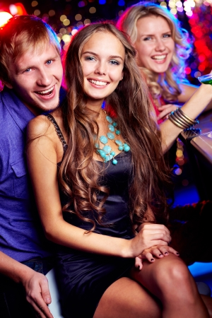 friends at bar: Image of happy friends looking at camera in bar Stock Photo