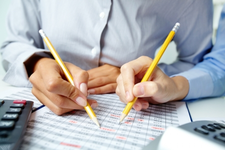 Photo of human hands holding pencils and pointing at numbers in documents  photo