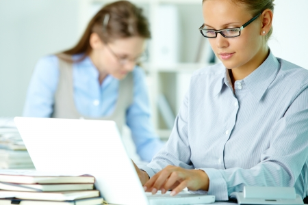 Portrait of pretty secretary working with laptop in office photo