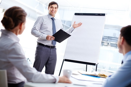 new strategy: Smiling business man presenting his new strategy to the colleagues