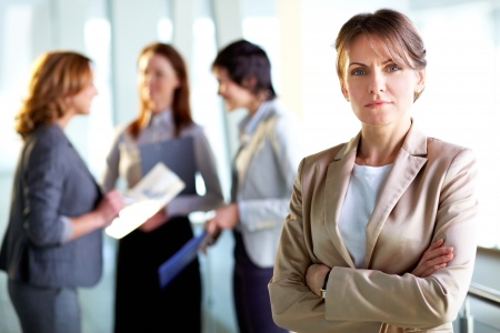 determined: Portrait of a mature business lady standing in the foreground, her female colleagues having a talk in the background Stock Photo