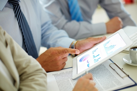 gadget: Businessman pointing at the screen of the touchpad with digital charts and graphs