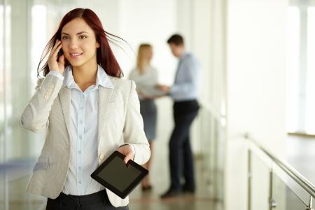 answering phone: Business lady contestar el tel�fono con una sonrisa con el equipo de trabajo en el fondo Foto de archivo