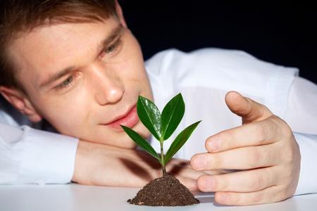 adverso: Cuidar el hombre joven la protecci�n de brote verde de las condiciones adversas