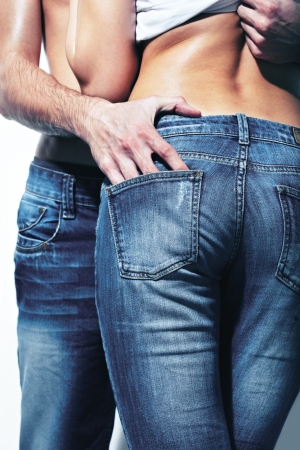 sensuality: Vertical shot of a seductive couple wearing jeans which accentuate beautiful form