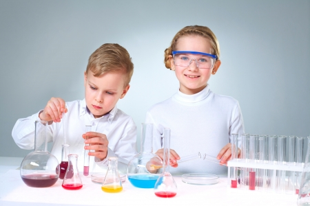 experimenting: Lovely children doing homework experimenting with substances and samples