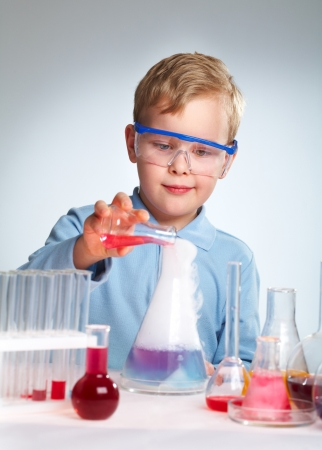 experiment: Schoolboy performing a risky experiment with boiling substances Stock Photo