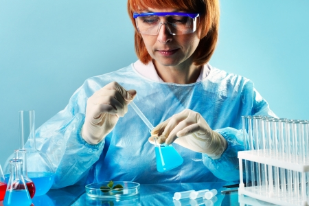 Female researcher studying sample of a plant and its interaction with chemical substances photo
