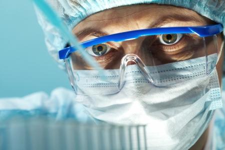 investigador cientifico: Trabajador de laboratorio hembra mirando a la pipeta con una muestra de sustancia Foto de archivo
