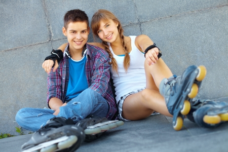 boy skater: Teenage boy and girl having a rest after roller-skating