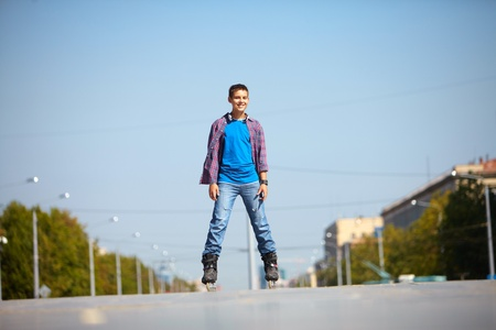 Handsome young man skating in urban surroundings photo