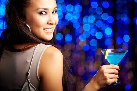 fashionable girl: Close-up portrait of a smiling girl holding a cocktail Stock Photo