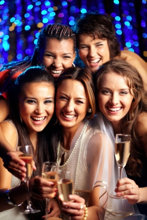 brindisi champagne: Tiro verticale di un gruppo di giovani donne che hanno divertimento alla festa di nozze