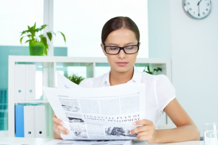 Portrait of a beautiful business lady reading newspaper photo