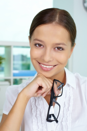 Portrait of pretty businesswoman smiling at camera with eyeglasses in hand photo