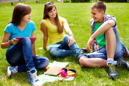 Cute high-school students doing homework outdoor on the lawn photo