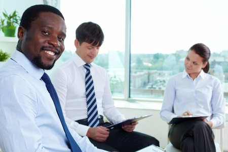 Portrait of successful boss looking at camera in working environment photo