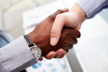 mani che si stringono: Close-up di uomini d'affari si stringono la mano, caucasici e afro-americano