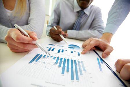 Gli uomini d'affari che parlano le tabelle e grafici che mostrano i risultati del loro lavoro di squadra riuscito