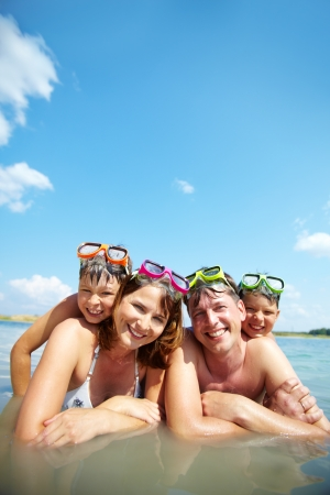 Photo of happy family looking at camera on resort photo