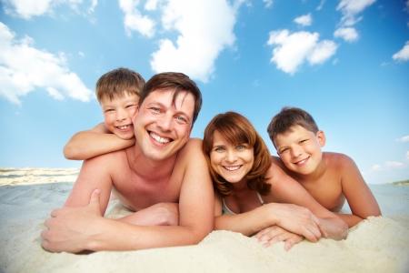 familia viaje: Foto de familia feliz acostado en la playa y mirando a la c�mara