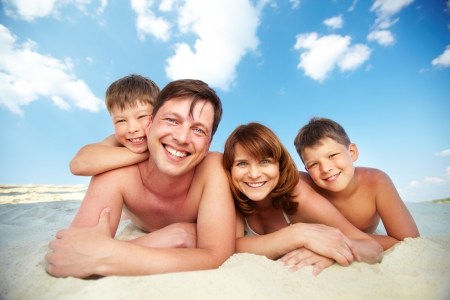 family photo: Photo of happy family lying on the beach and looking at camera Stock Photo
