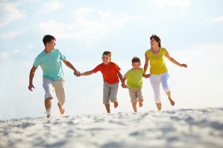 viaje familia: Foto de familia feliz corriendo por la playa en verano