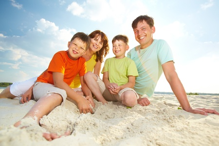 Photo of happy family sitting on sand during summer rest photo