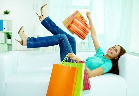 spree: Portrait of happy shopper with paperbags lying on sofa and looking at camera Stock Photo