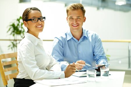 career success: Handsome guy and his pretty colleague looking at camera while solving some business matters