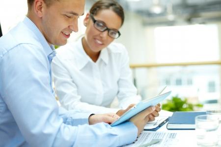 colaboracion: Hombre de negocios joven mirando touchpad con su secretaria cerca