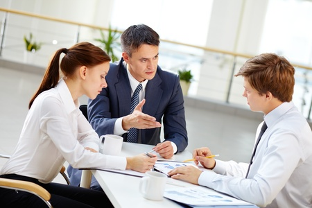 apprentice: Mature team leader motivate young employee by gesture to share his business ideas Stock Photo