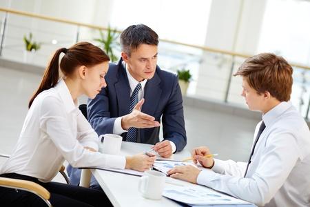 Oudere teamleider motiveren jonge werknemer door middel van gebaren om zijn zakelijke ideeën te delen